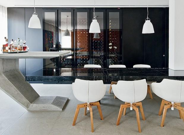 Na sala de jantar, a mesa é um prolongamento da bancada de mármore e tem apoio metálico central. A mesa-bar, desenhada pelos arquitetos do escritório Zemel + Chalabi , é de concreto moldado. Destaque para a adega climatizada... na cor preta (Foto: Maíra Acayaba/Casa e Jardim)