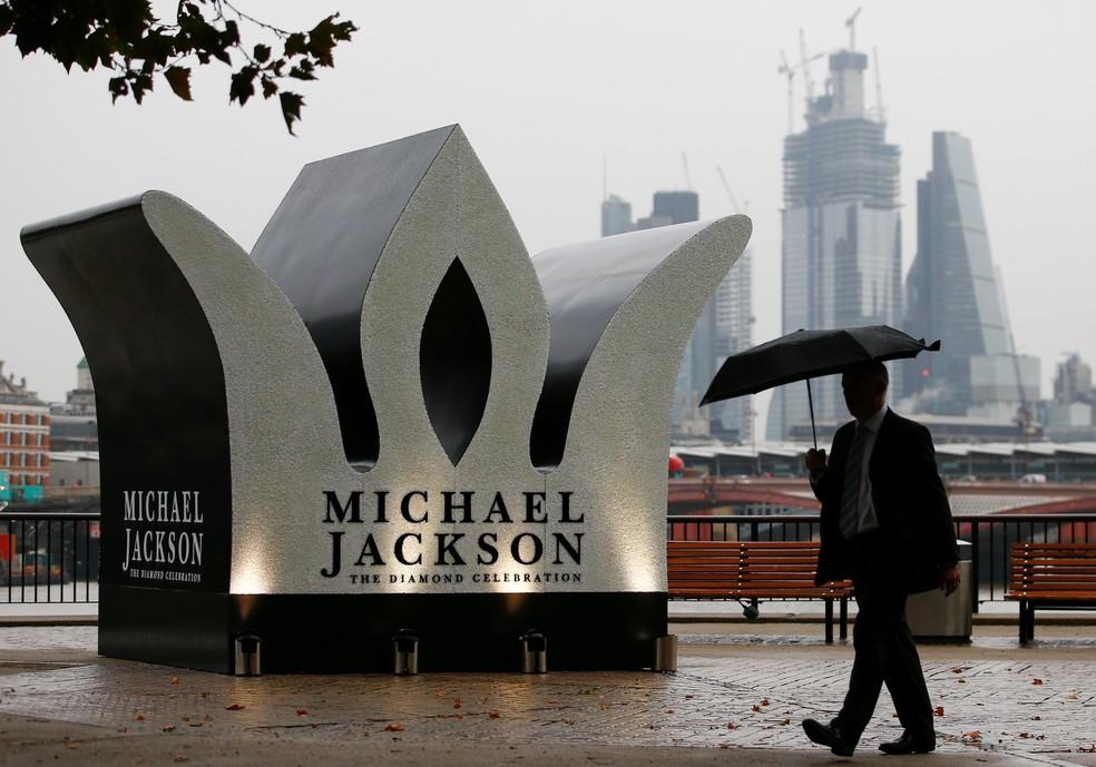 Um homem passa por coroa gigante instalada para celebrar o 60º aniversário de Michael Jackson, na margem sul de Londres (Foto: REUTERS/Henry Nicholls)