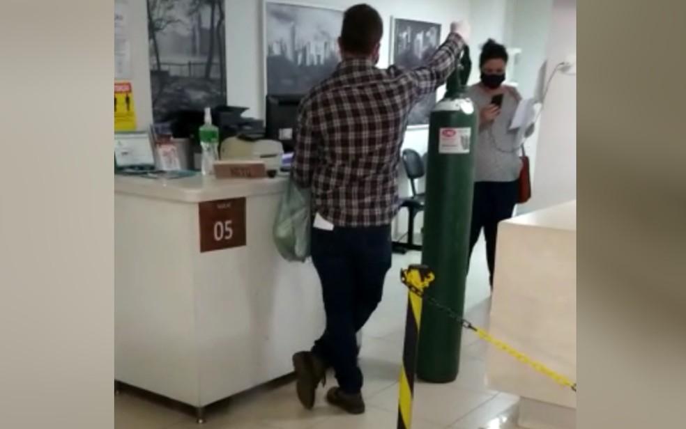 Parente leva cilindro de oxigênio para paciente internado em hospital particular em Goiânia — Foto: Reprodução/TV Anhanguera
