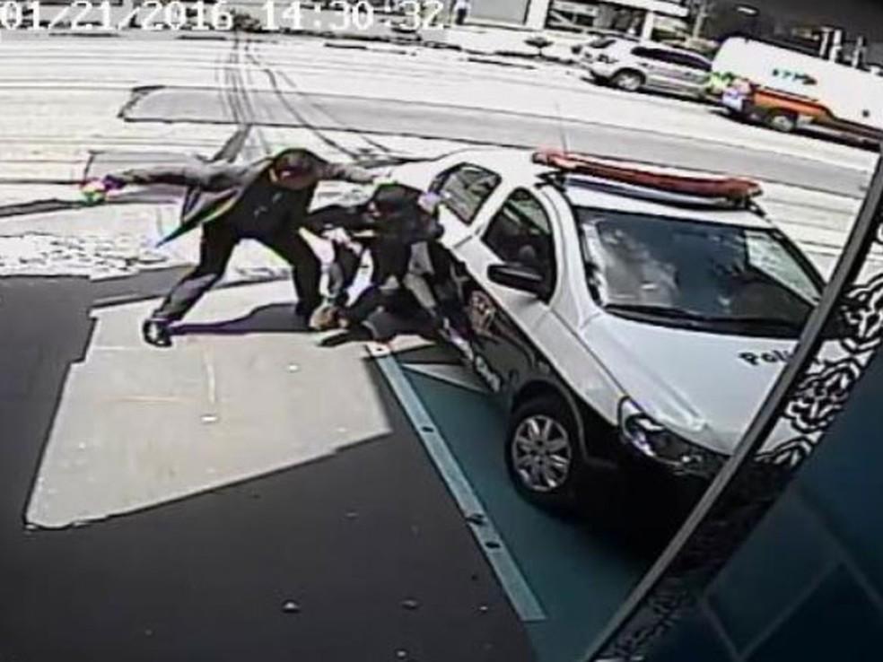 José Camilo Leonel dá socos em Navid Saysan ao lado de viatura policial — Foto: Reprodução/Câmera de Segurança