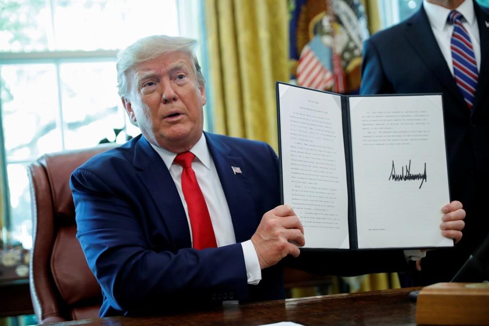 Donald Trump exibe assinatura em ordem executiva que impõe novas sanções ao Irã — Foto: Carlos Barria/Reuters