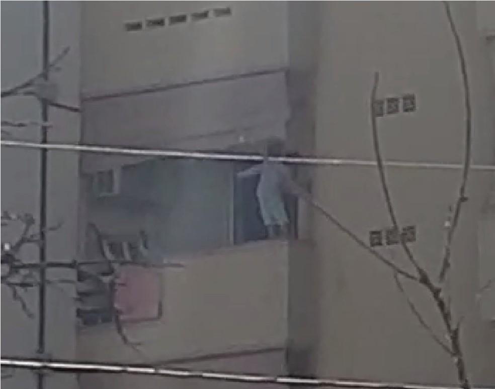 Menino estava pendurado na tela de segurança de apartamento — Foto: Reprodução