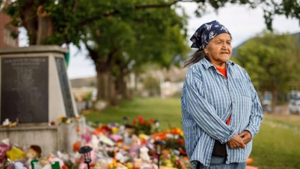 Sobrevivente da escola Kamloops, Evelyn Camille posa ao lado de memorial das vítimas do lugar — Foto: Cole Burston/BBC