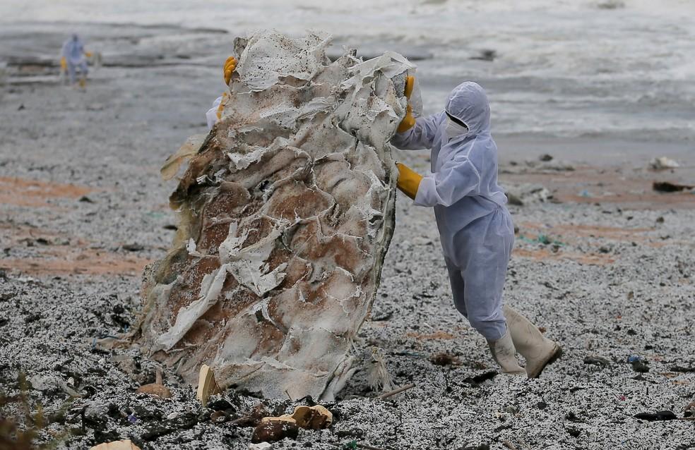 Membro da marinha do Sri Lanka remove lixo que chegou a uma praia do país, em 28 de maio de 2021 — Foto: Dinuka Liyanawatte/Reuters