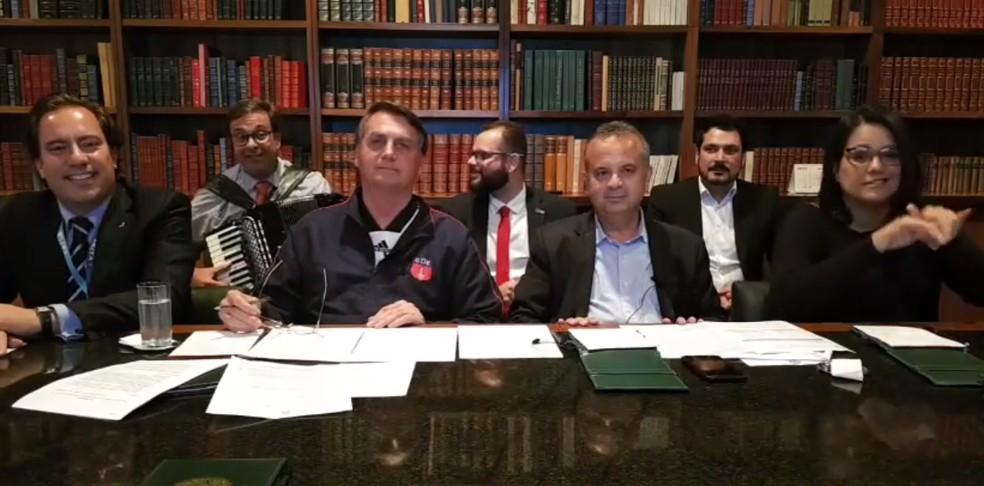 Bolsonaro apresentou uma live na quinta-feira (2), ao lado do presidente da Caixa Econômica Federal, Pedro Guimarães (à esquerda), e do ministro do Desenvolvimento Regional (Rogério Marinho), à direita. Ao fundo, o presidente da Embratur tocou e cantou a música 'Riacho do Navio', com alterações da letra — Foto: Reprodução