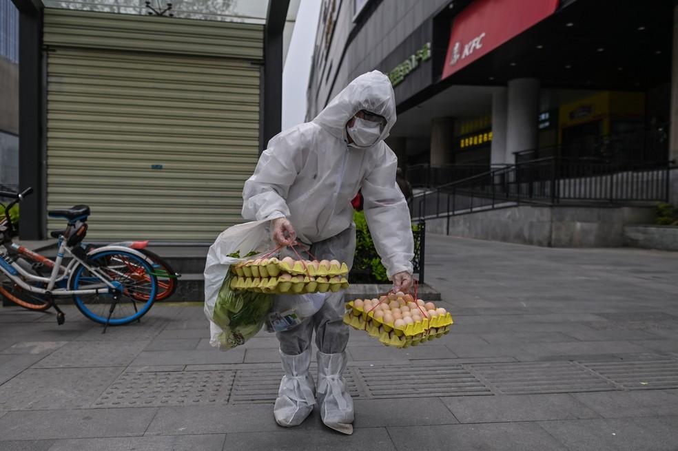 Pessoa com traje de proteção caminha em uma rua em Wuhan, na China, nesta sexta-feira (3)  — Foto: Hector Retamal / AFP