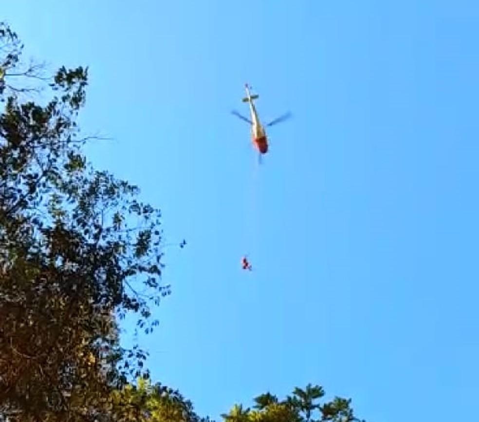 Mulher de 46 anos foi levada de helicóptero após queda de cachoeira em Pedralva (MG) — Foto: Corpo de Bombeiros