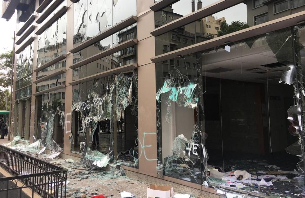 Prédios comerciais amanheceram com vidros quebrados em Santiago neste domingo (20) — Foto: Adriane Schultz/G1