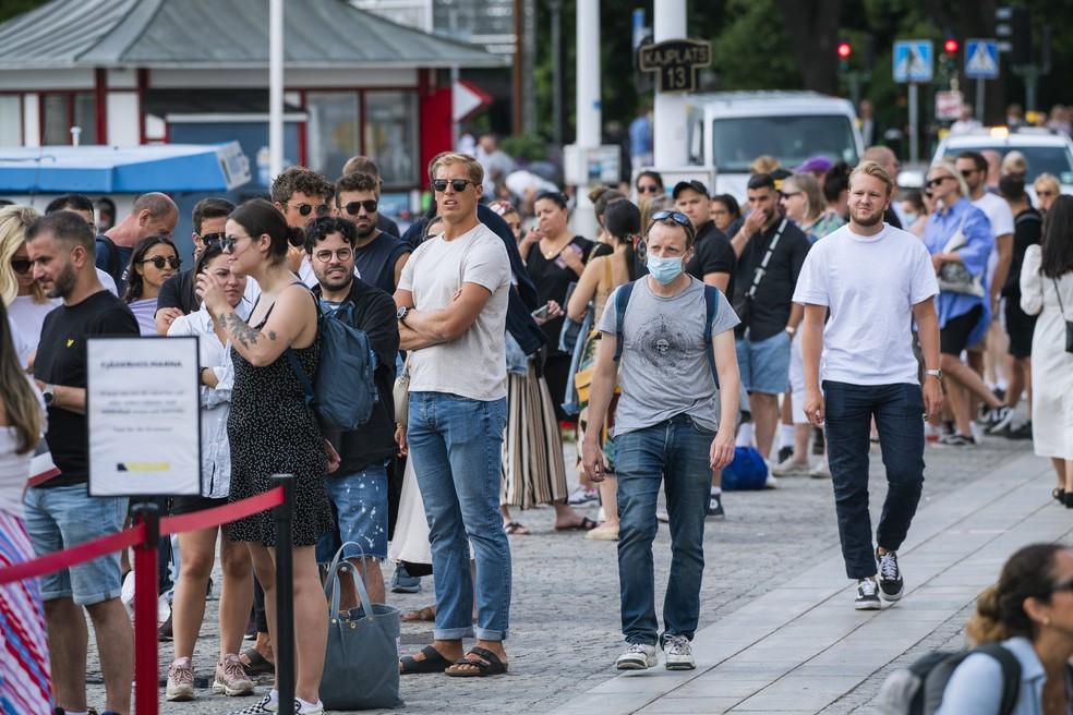 Foto de arquivo de 27 de julho mostra um homem usando uma máscara protetora ao lado de pessoas em uma fila para embarcar em Estocolmo, na Suécia, em meio à nova pandemia de coronavírus — Foto: Jonathan Nackstrand/AFP