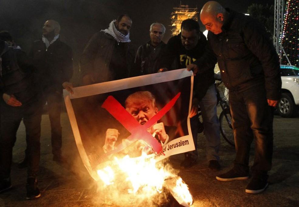 Palestinos protestam queimando a foto do presidente Donald Trumpe, Belém, na terça-feira (5)  (Foto: Musa Al Shaer / AFP)