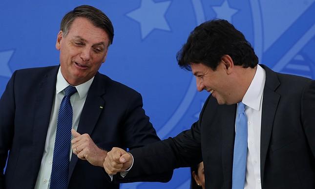 O então ministro da Saúde, Luiz Henrique Mandetta (à dir.), cumprimenta o presidente Jair Bolsonaro durante cerimônia de posse de seu sucessor, Nelson Teich, em abril de 2020