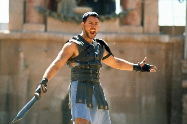 O ator Russell Crowe com a armadura de seu personagem em Gladiador (1999) que ele colocou em leilão (Foto: Reprodução)