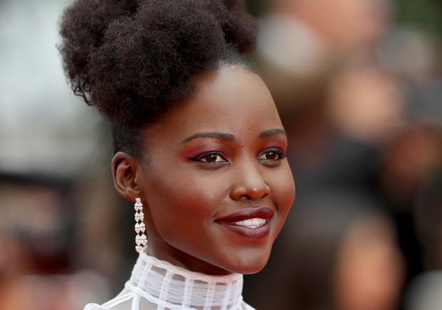 O make de Lupita Nyong'o tem pele bem feita, sombra vermelha, delineador estilo gatinho e lábios vinho (Foto: Getty Images)