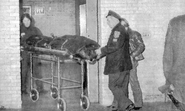 O corpo de John sendo removido do hospital para o necrotério de Nova York