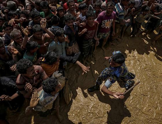 Policial tenta controlar grupo rohingya que aguardava ajuda em Cox's Bazar (Foto: FOTÓGRAFOS/REUTERS)
