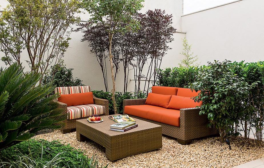 Murtas enfileiradas camuflam o guarda-corpo da escada que leva à garagem e criam uma moldura para o sofá laranja da Amazônia Móveis. A poltrona e a mesa são da mesma marca. Projeto de paisagismo de Edu Bianco, da Flamboyant Paisagismo e dos arquitetos da Cactus Arquitetura e Urbanismo