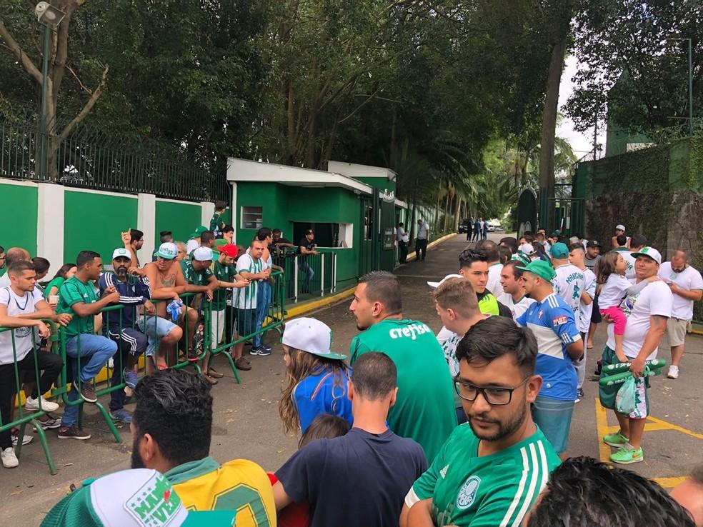 Torcedores do Palmeiras aguardam a saída da equipe na Academia de Futebol — Foto: Renato Cury