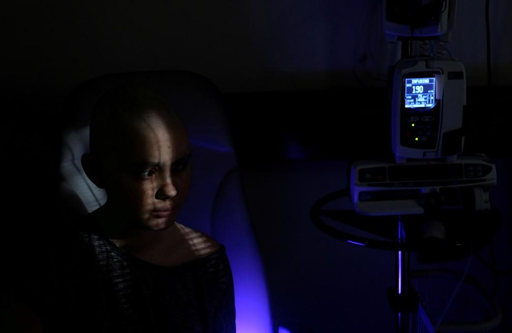 Rebecca Zammit Lupi, uma paciente com câncer de 14 anos, recebe um gotejamento intravenoso de hidratação após uma sessão de quimioterapia em seu quarto na ala Rainbow do Centro Oncológico Sir Anthony Mamo, no Hospital Mater Dei em Tal-Qroqq, Malta, em 15 de junho — Foto: Darrin Zammit Lupi/Reuters