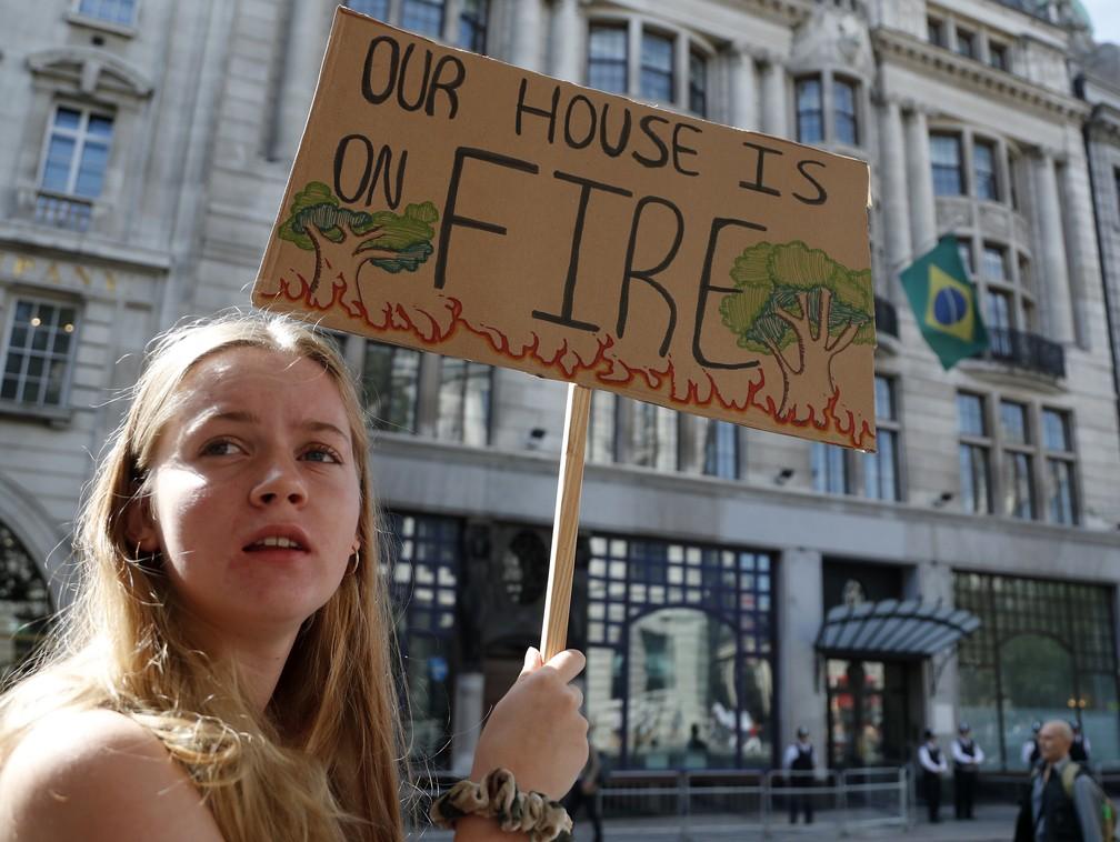 """Manifestante da Extinction Rebellion segura placa com a frase """"nossa casa está pegando fogo"""" em frente à embaixada brasileira em Londres nesta sexta-feira (23). — Foto: Frank Augstein/AP"""