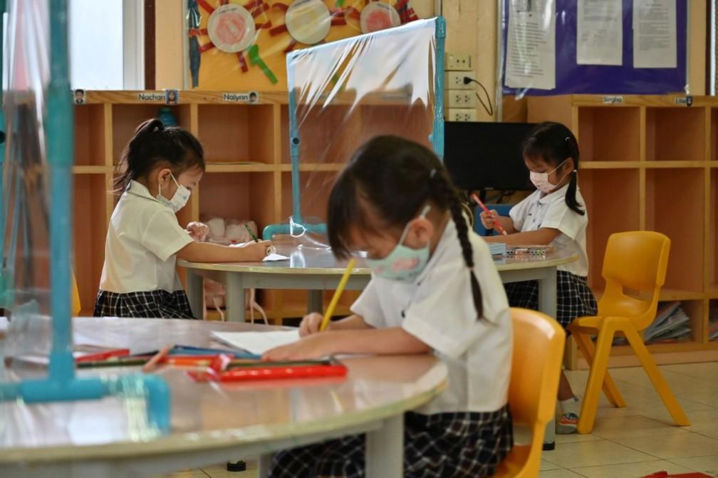 Alunos que frequentam sala de aula equipada com mesas com divisórias de plástico para impedir a propagação do novo coronavírus em escola em Bangkok, na Tailândia, em 17 de junho  — Foto: Romeo Gacad / AFP