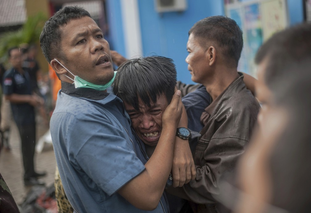 Homem chora após identificar parente entre os corpos de vítimas do tsunami em Carita, Indonésia — Foto: Fauzy Chaniago/AP Photo