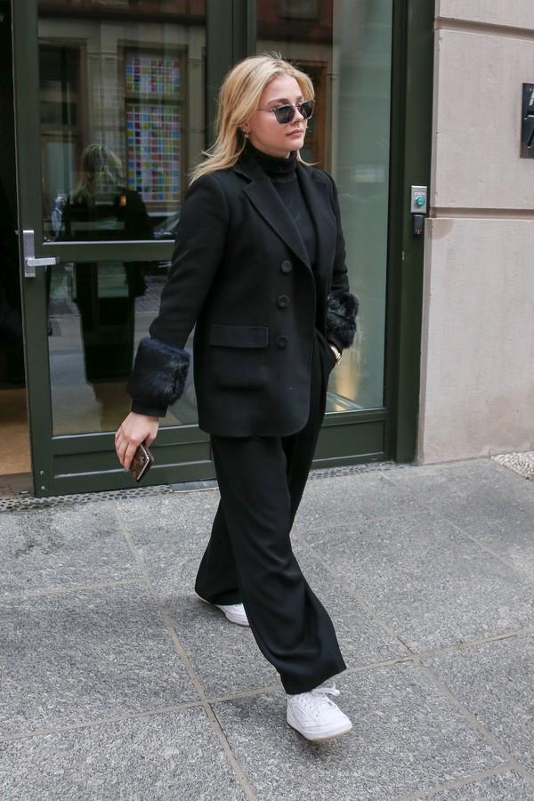 Chloe Moretz de terno preto com os punhos do paletó de pele, combinado com tênis branco Reebok e e gola rolê num look bem 90s. (Foto: IMAXTREE)