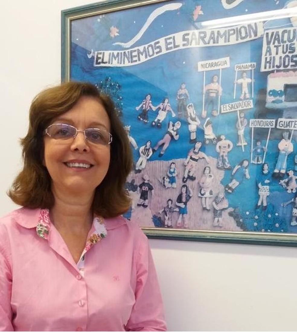 Marilda com quadro da campanha contra sarampo que fica em sua sala: 'Brasil foi luz no fim do túnel para outros países' — Foto: Vinicius Ferreira/IOC/Fiocruz/Via BBC