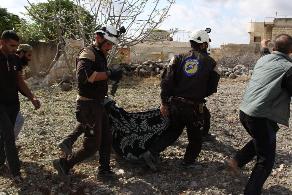 Membros da Defesa Civil da Síria carregam os corpos das vítimas de um ataque aéreo russo na vila de Jaballa, sul de Idlib, neste sábado (02) — Foto: Abdulazez Ketaz/AFP