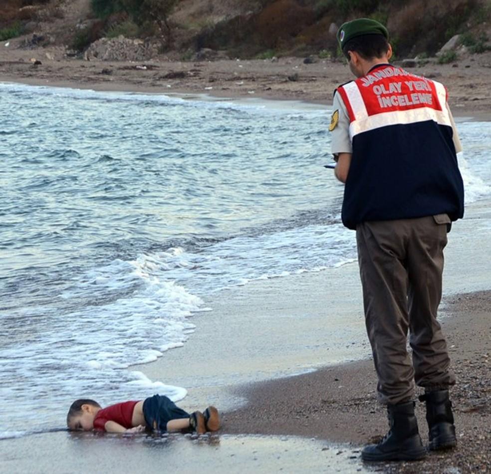 Policial paramilitar turco investiga o local onde apareceu o corpo de uma criança imigrante numa praia de Bodrum, na Turquia (Foto: AP Photo)