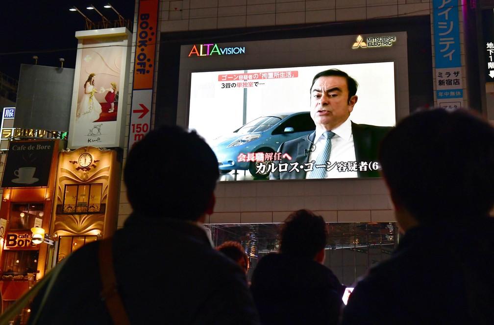 Japoneses assistem reportagem sobre Carlos Ghosn nas ruas de Tóquio nesta quinta-feira (22) — Foto: Kazuhiro Nogi / AFP