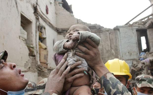 Foto de domingo (26) mostra o bebê Sonit Awal sendo retirado dos escombros de sua casa após ficar 22 horas soterrado no Nepal (Foto: Amul Thapa/Kathmandu Today via AP)