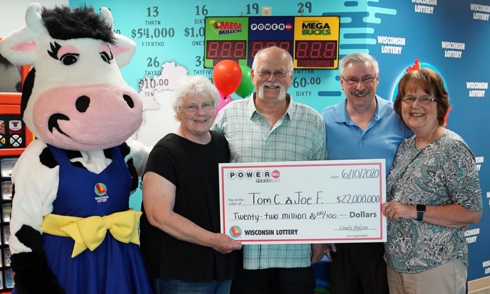 Tom Cook e Joseph Feeney posam com suas esposas segurando um cheque representando o prêmio no valor de 22 milhões de dólares — Foto: Wisconsin Lottery/Divulgação