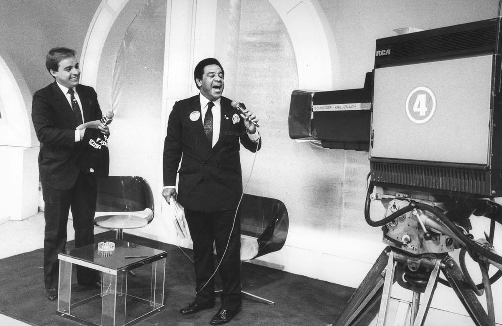 Gugu Liberato recebe o cantor Agnaldo Timóteo durante gravação de seu programa nos estúdios do SBT em São Paulo, em agosto de 1986 — Foto: Oswaldo Maricato/Estadão Conteúdo/Arquivo