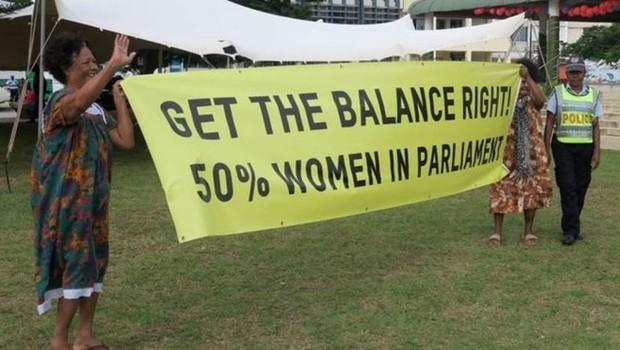 Mulheres em Vanuatu exigem representação igualitária: cartaz defende que mulheres ocupem metade das vagas no Parlamento (Foto: Getty Images/BBC)