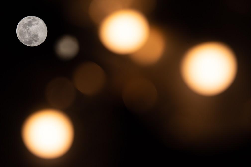 Lua cheia vista entre as luzes em Stuttgart, na Alemanha — Foto: Sebastian Gollnow/AFP