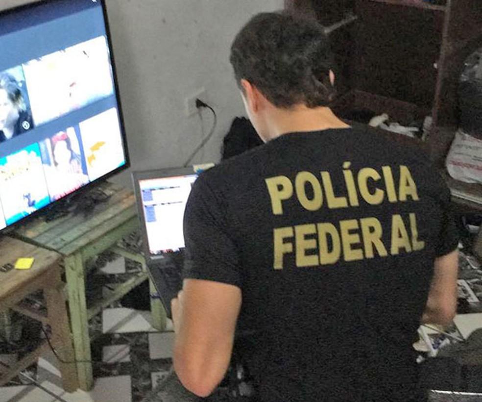 Policial federal analisa computador de suspeito de pornografia infantil em Iguape, SP — Foto: Divulgação/PF