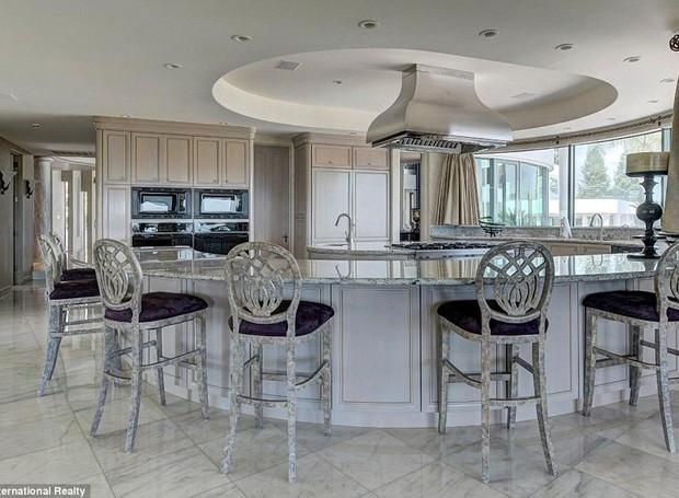 As janelas iluminam a cozinha com a luz natural e o roxo das poltronas contrasta com a cor clara do resto dos móveis e armários