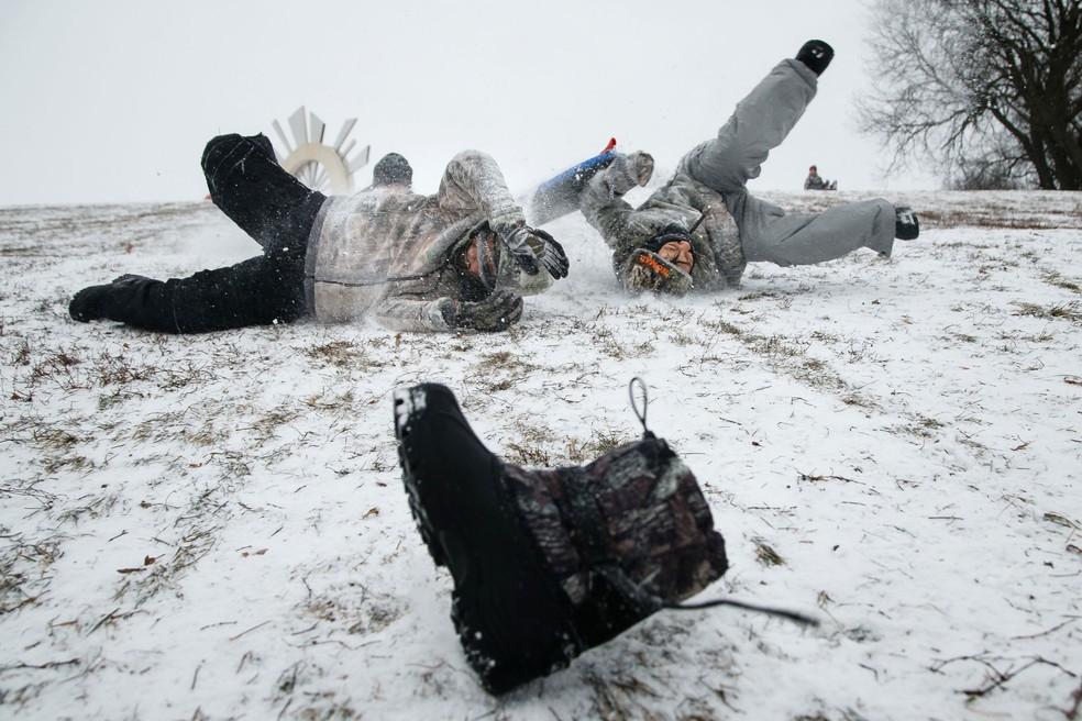 Irmãos brincam na neve em Des Moines, nos Estados Unidos, na sexta-feira (29)  (Foto: Brian Powers/The Des Moines Register via AP)