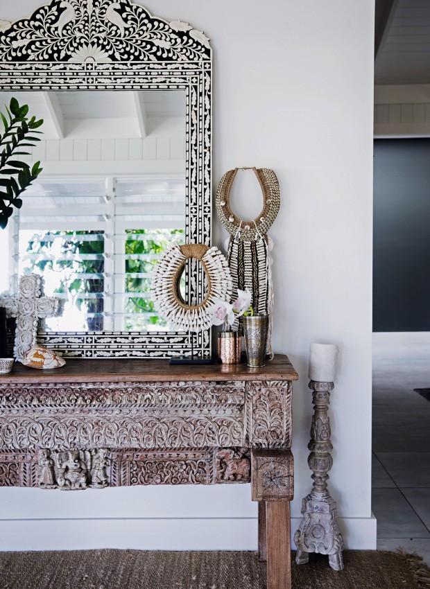 Entrada. A combinação de espelho com moldura de ossos, mesa de madeira entalhada, velas e colares étnicos dá as boas-vindas a quem chega à casa (Foto: Chris Warnes Warnes & Walton / Living Inside)
