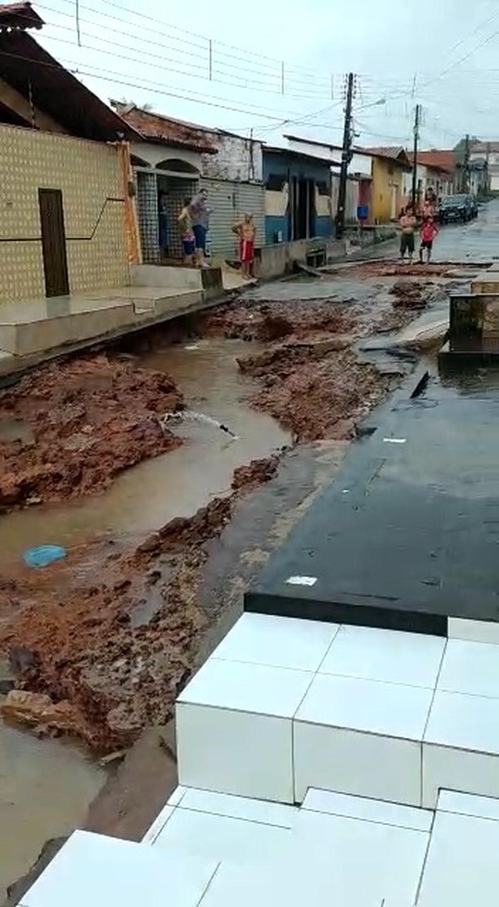 Após a chuva diminuir, moradores observam o estrago feito na mesa rua da imagem acima — Foto: Divulgação