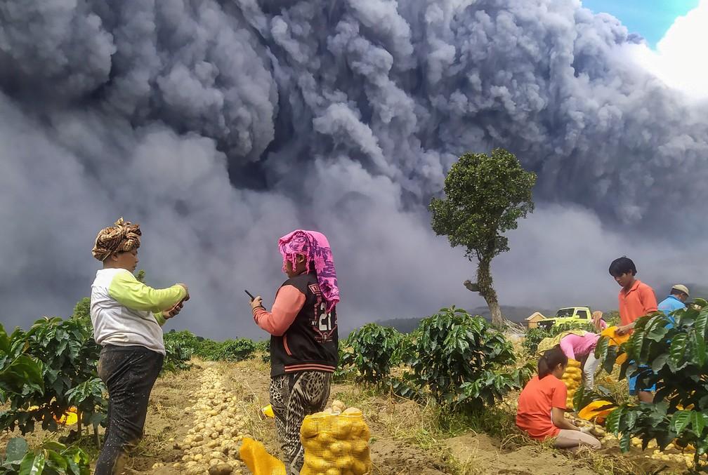 Agricultores observam nuvem de fumaça de vulcão na Indonésia, em 10 de agosto de 2020 — Foto: Antara Foto/Sastrawan Ginting/ via Reuters