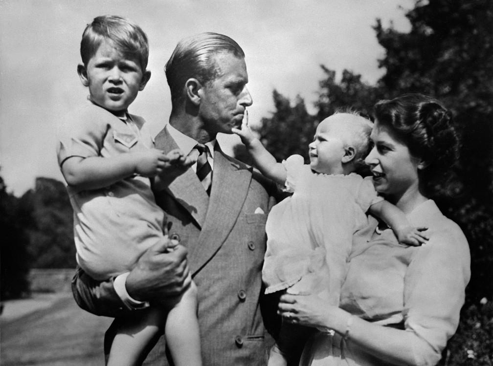 O príncipe Philip segura o filho Charles no colo ao lado da esposa, a rainha Elizabeth, com a filha Anne, em foto de 1952 — Foto: AFP