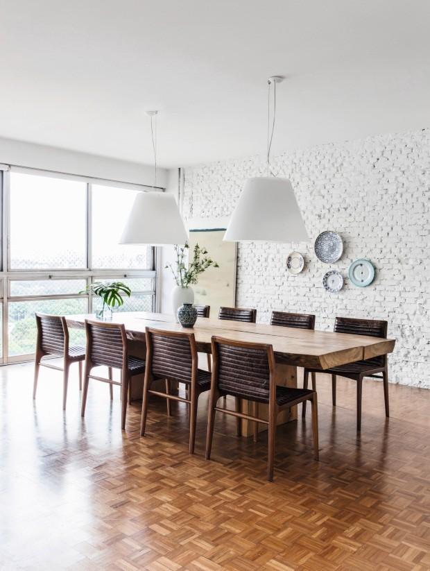 Os arquitetos Marina Acayaba e Juan Pablo Rosenberg pintaram de branco a parede de tijolos, original do apartamento, para enfatizar a luz natural que entra na sala de estar e destacar as peças de design (Foto: Maíra Acayaba / Editora Globo)