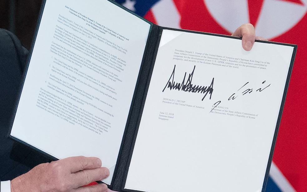 Donald Trump exibe o documento assinado por ele e Kim Jong-Un em Singapura, na terça-feira (12) (Foto: Saul Loeb/AFP)
