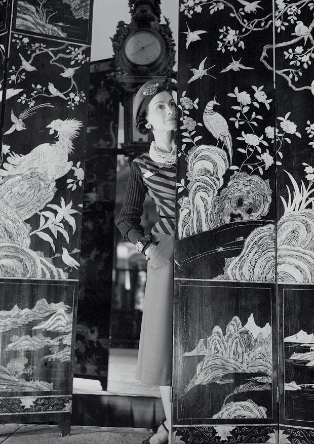 Coco Chanel em 1937, entre os painéis que inspiram agora as peças da alta-joalheria da maison (Foto: © Boris Lipnitzki / Roger-viollet / Chanel Fine Jewelry/ Getty Images)