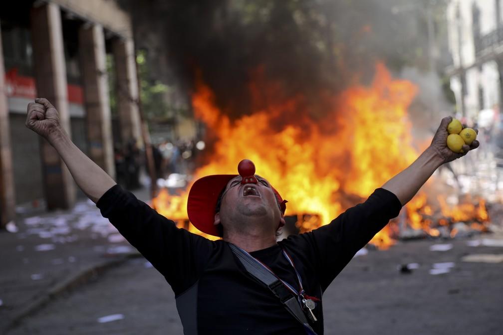Manifestante vestido de palhaço grita em frente a barricada no centro de Santiago, no Chile, nesta terça-feira (22) — Foto: Rodrigo Abd/AP Photo