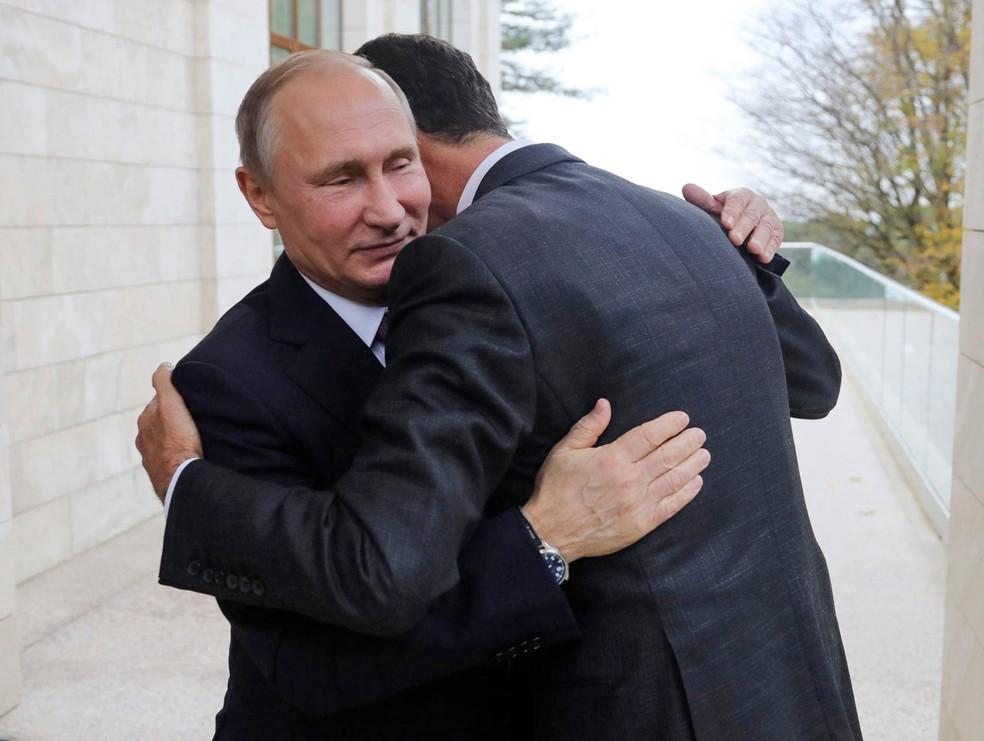 Os presidentes da Rússia e da Síria, Vladimir Putin (esq.) e Bashar al.Assad, se abraçam em encontro na residência presidencial russa Bocharov Ruchei no Mar Negro — Foto: Mikhail Klimentyev/Kremlin pool via AP