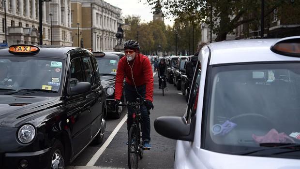 Ciclista usa máscara em meio ao trânsito de Londres: capital inglesa vai implantar pedágio para carros poluentes (Foto: Carl Court/Getty Images)