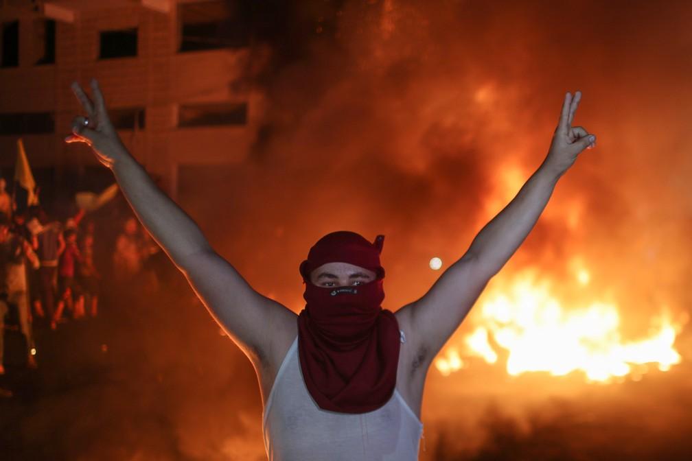 Palestino durante protesto na Cidade Velha de Jerusalém; ao fundo, pneus queimam — Foto: Mohammed Salem/Reuters