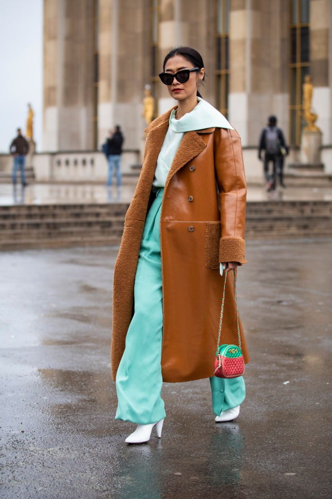 "Verde menta com <a href=""https://revistamarieclaire.globo.com/Moda/noticia/2019/08/dez-looks-com-trench-coat-para-te-inspirar.html"">trench coat</a> caramelo (Foto: Getty)"